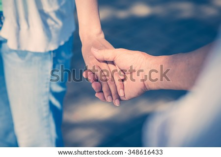 Senior man holding hand of his adult daughter