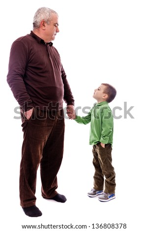 Senior man holding his grandson's hand, both with one hand in pocket, isolated on white background - stock photo