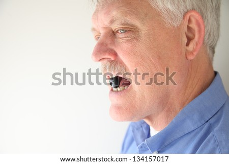 senior man holds fresh blueberry in his teeth