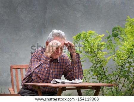 Senior man holds hands on forehead - stock photo