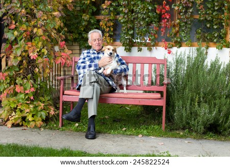 Senior man hugging his dog on his lap on bench - stock photo