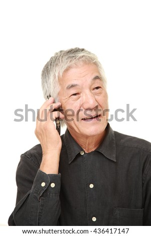 senior man in a black shirts with a smart phone