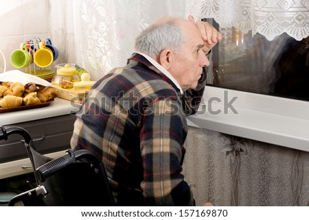 Senior man in a wheelchair peering through a window at night with his hand raised to his forehead to cut the light reflections on the glass - stock photo