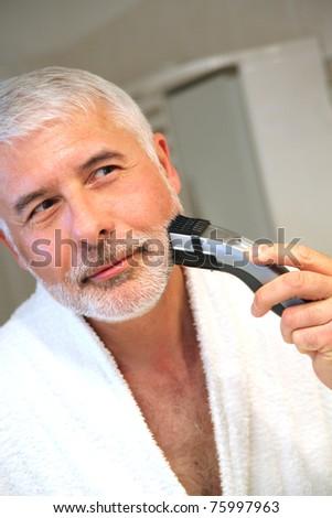 Senior man in bathroom with electric razor - stock photo