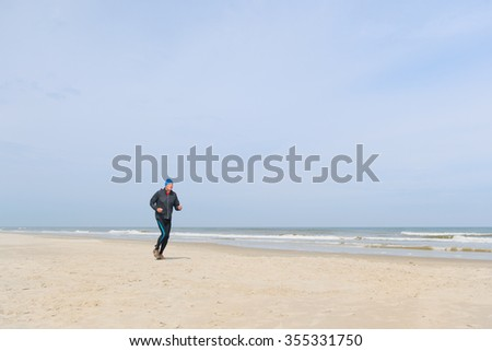 Senior man in black clothes running at the beach - stock photo