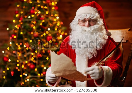 Senior man in costume of Santa Claus writing Christmas letter - stock photo