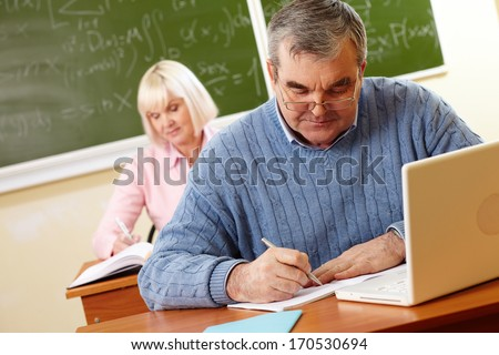 Senior man in eyeglasses carrying out written task in classroom - stock photo