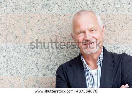 Senior man in front of a wall