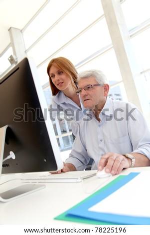 Senior man in front of desktop computer - stock photo