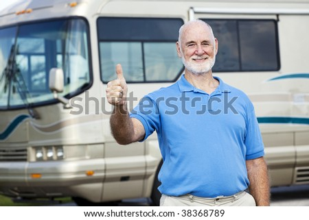 Senior man in front of his luxury motor home gives the thumbs up sign. - stock photo