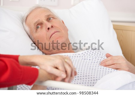 Senior man in hospital bed holding wife's hand - stock photo