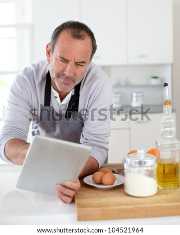 Senior man in kitchen using electronic tablet