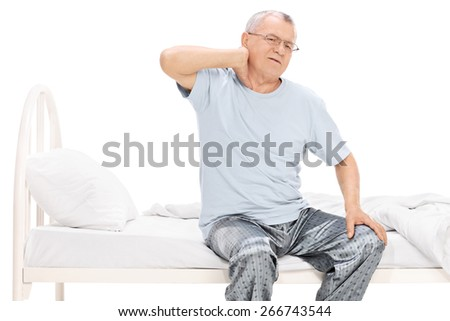 Senior man in pajamas feeling pain in his neck seated on a bed isolated on white background - stock photo