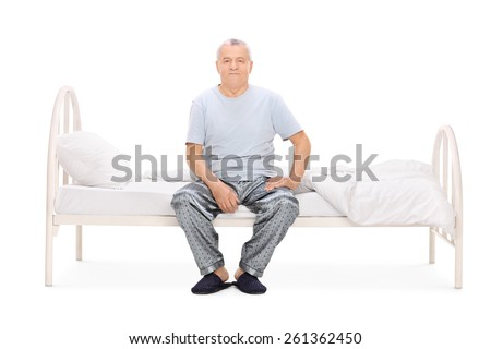Senior man in pajamas sitting on a bed isolated on white background - stock photo