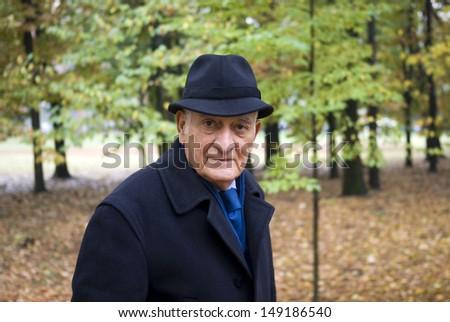 Senior man in park in autumn - stock photo