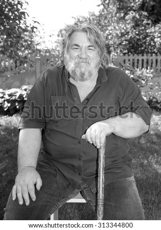 Senior man in park. Portrait of smiling aged caucasian man with a gray beard on green park background. Smiling old man with a grey beard. Black and white image.  - stock photo
