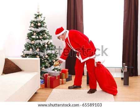 Senior man in Santa Claus uniform, putting a gift from bag under the decorated christmas tree