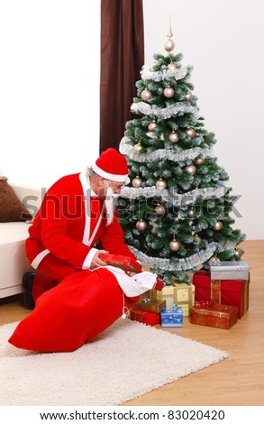 Senior man in Santa Claus uniform, putting presents under Christmas tree from bag