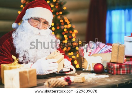 Senior man in Santa costume packing presents and looking at camera - stock photo