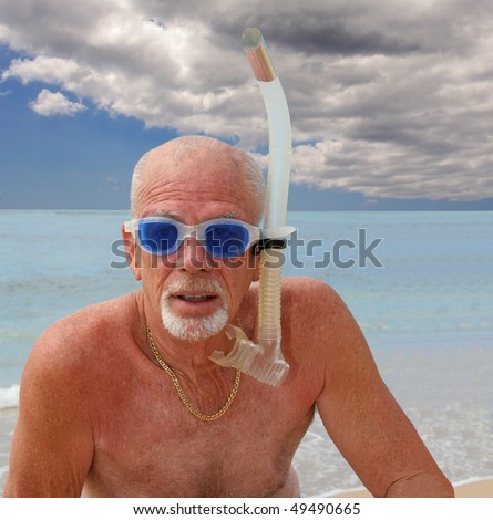 Senior man in snorkel and blue goggles at the ocean shore