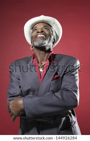 Senior man in suit and fedora looking up against red background - stock photo
