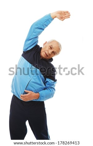Senior man in training suit doing warm-up stretching exercises