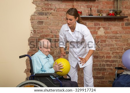 Senior Man In Wheelchair Holding Spiky Ball During Physiotherapy - stock photo