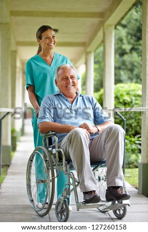 Senior man in wheelchair with nurse in the park of a hospital - stock photo