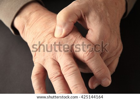 Senior man indicates where he feels pain on the back of his hand. - stock photo
