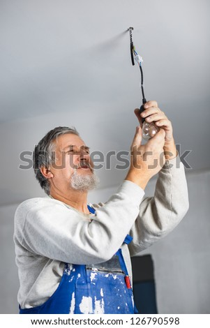Senior man installing a bulb in a freshly renovated appartment - stock photo