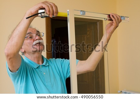 senior man installing and measuring a shower box at home, do-it-yourself concept