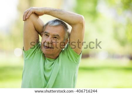 Senior man is exercising in park. Active retirement. - stock photo