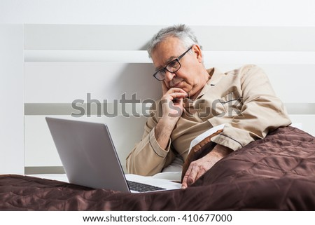 Senior man is lying in bed and using laptop