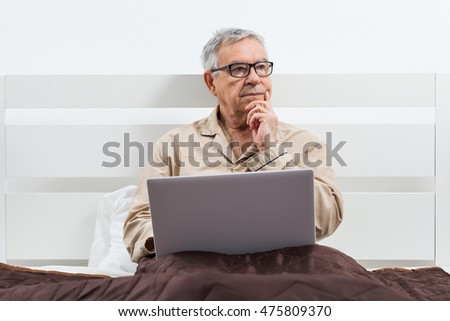 Senior man is lying in bed and using laptop.