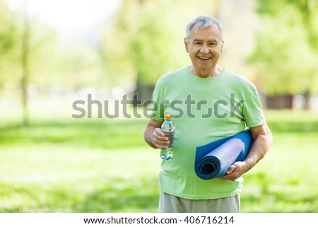 Senior man is ready for exercise in park. Active retirement. - stock photo