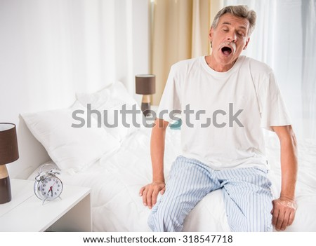 Senior man is sitting in bed and yawning. - stock photo