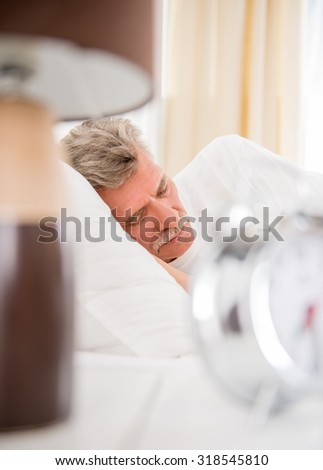 Senior man is sleeping in comfortable bed at home. - stock photo