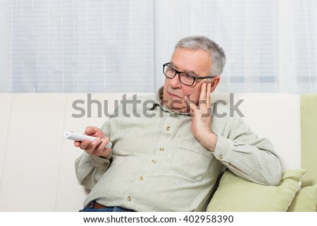 Senior man is trying to find something interesting on tv to pay his attention,but there is nothing interesting.I'm so bored! - stock photo