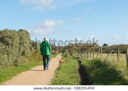 Senior man is walking the dog in nature - stock photo