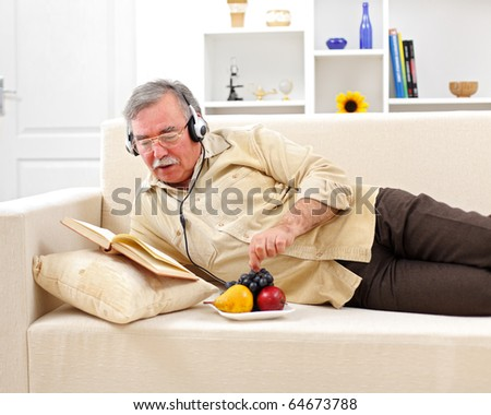 Senior man laying on sofa, reading and listening to music while eating fruits