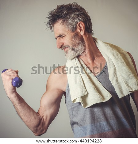 Senior man lifting one kilo dumbbell pretending it's heavy one  - stock photo