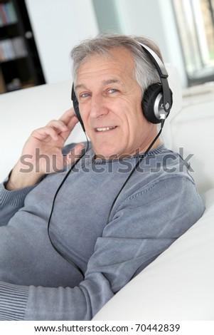 Senior man listening to music with headphones - stock photo