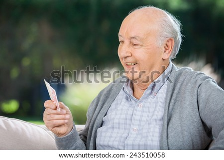 Senior man looking at cards while sitting on couch at nursing home porch - stock photo