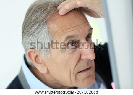 Senior man looking at hair loss in mirror - stock photo