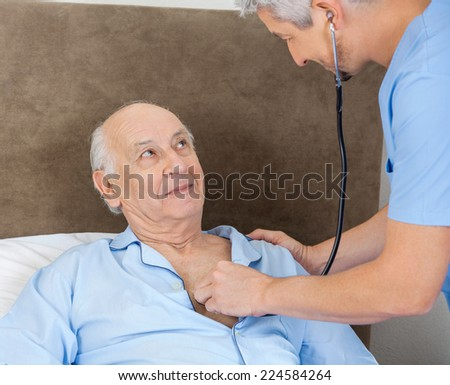 Senior man looking at male caretaker examining him with stethoscope at nursing home