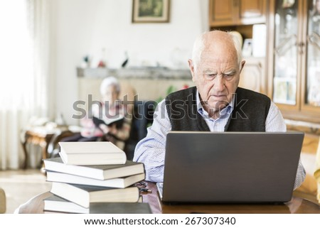 Senior man looking for information in books and internet - stock photo