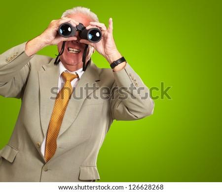 Senior Man Looking Through Binoculars On Green Background - stock photo