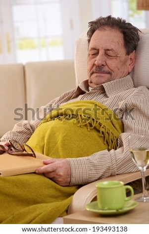 Senior man lying in armchair at home, sleeping in afternoon sunlight. - stock photo