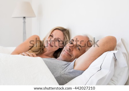 Senior man lying on bed next to beautiful mature woman. Happy smiling couple lying on bed on a bright sunny morning. Senior man looking at camera and relaxing with his wife on bed.