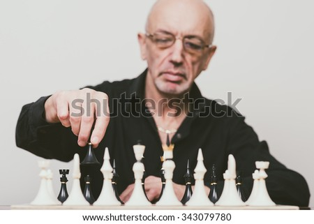 Senior man making move at chess game (focus on the hand holding chess piece)